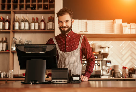 Cheerful bearded bartender near cash register