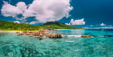 Spoed Fotobehang Nachtblauw Grand Anse beach at La Digue island in Seychelles. Turquoise blue lagoon and exotic tropical island in background.