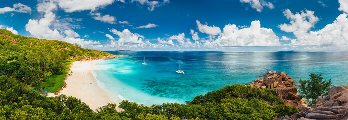 Spoed Fotobehang Strand Aerial Pano of Grand Anse beach at La Digue island in Seychelles. White sandy beach with blue ocean lagoon and catamaran yacht moored