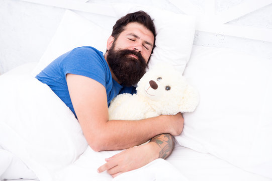 lazy hipster relax in bedroom. good night and sweet dreams. bearded man teddy bear in bed. plush toy concept. happy birthday present. time go to sleep. spend weekend in bed. feel cosy at home
