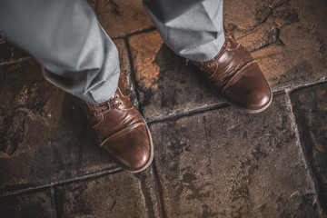 Top view of a man wearing brown leather shoes and grey dress pants.