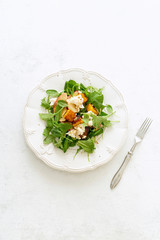 Overhead image of healthy salad with baked pumpkin and apples