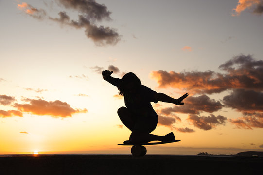 Silhouette of a guy balancing on a balance board
