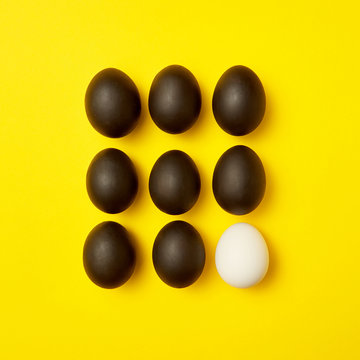 Easter yellow background with pattern of black eggs and one white. Copy space.