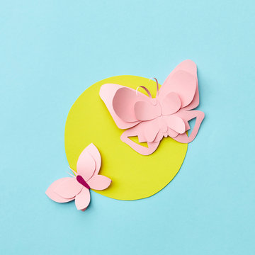 Handmade paper pink butterflies on a yellow round frame on a light blue background with copy space. Flat lay