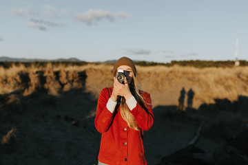 Woman pointing vintage camera straight forward