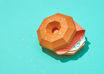 Paper origami handmade sandwich with red fish on a turquoise background.