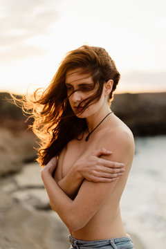Young naked woman standing on rock cliff near sea