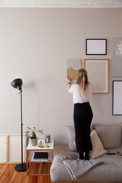 A woman hang a painting ( Wall art belong to owner)