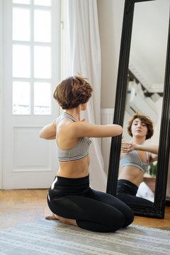 Woman twisting torso near mirror