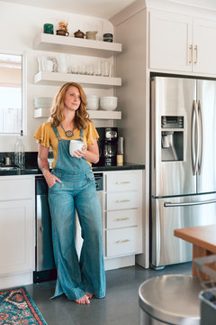 Young redhead woman stands in her modern kitchen and leans against the counter while holding a mug.