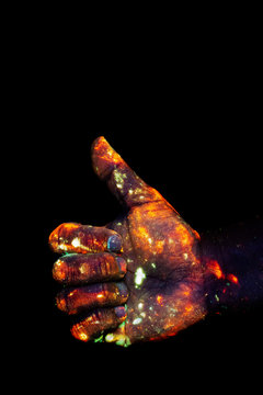 Male hand painted with fluorescent paint glowing in the darkness