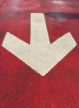 big white arrow on red floor