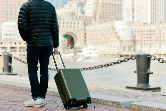 Man walking with suitcase in city
