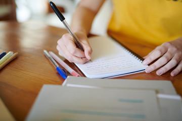 Crop girl writing in notepad doing studies