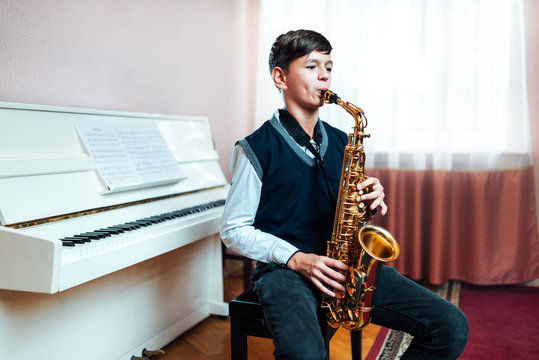 student boy plays saxophone while sitting at a music lesson in class