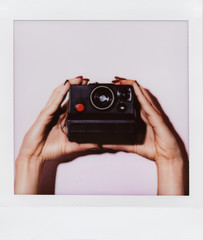 woman taking a picture with an instant camera