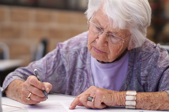 Older woman signing a document