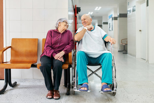 Senior couple waiting in a hospital, smiling