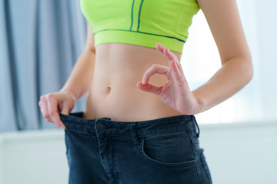 Healthy sport fitness woman with slim waist pulling her big jeans and showing losing weight results. Goal achievement, motivation and progress in slimming and diet