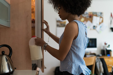 Young Black Woman Taking Milk from the Fridge . Lifestyle Stock Picture