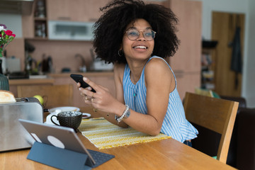Young Black Happy Woman Checking Her Mobile Phone in the Early Morning During Breakfast. Lifestyle Stock Picture