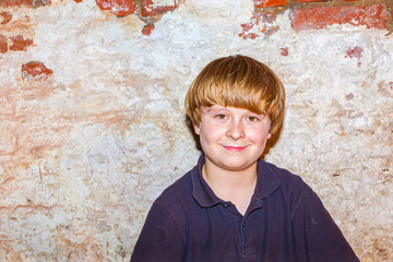 cute young boy with old brick wall background