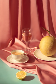 Melon wine and orange tea on pink background.
