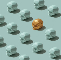 Set of gray skulls and one painted in golden skulls on a gray background . Creative background. Flat lay
