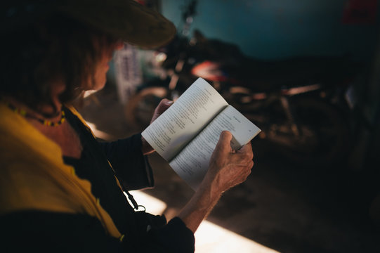 Mature man in cowboy hat reading poetry book