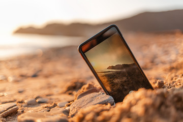 The concept of the photos on the phone. The smartphone lies buried in the sand on the beach, and takes a photo of the beach in the background. Copy space