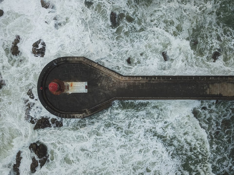 Drone view of lighthouse on pier in waves