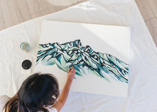 Overhead shot of female asian artist working on mountain painting in studio