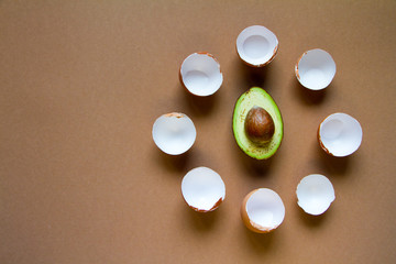 Fotobehang An eggshell of few brown chicken eggs around a half of ripe avocado, the concept of ketogenic nutrition, the image of the watch dial