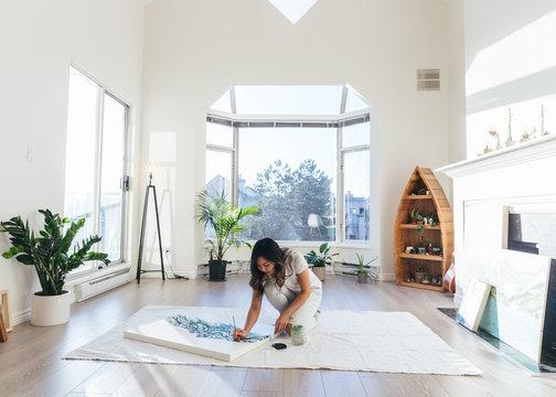 Female asian artist working on painting in minimalist studio