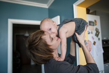 Happy mother holds her little child in her cozy room.