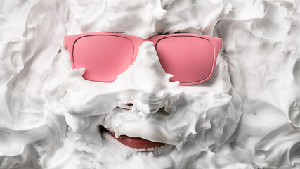 Portrait of a man with shaving foam and pink glasses
