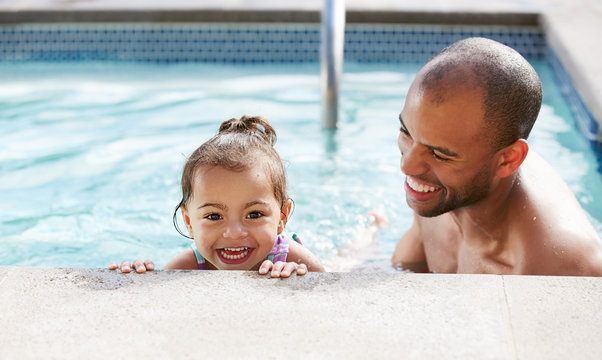 Ethnic father helping his young daughter learn to swim