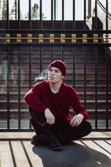 young man smoking, sitting on the street