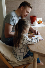 Father and daughter drawing at table together