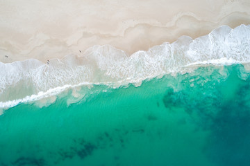 Aerial image of summertime beach scene of white sandy beach and clear clean turquoise waters
