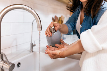 Mother helping daughter washing hands in kitchen