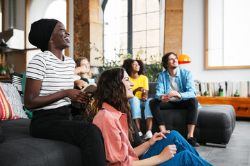 Friends sitting on sofa watching tv. Fotoväggar