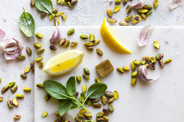 Cooking ingredients with pistachio nuts, herbs, stock cube and lemons