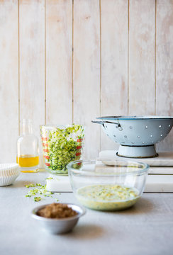 Kitchen surface with measured baking ingredients and blue colander
