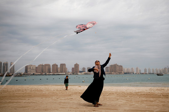 A Muslim woman flies a kite at Katara beach in Doha