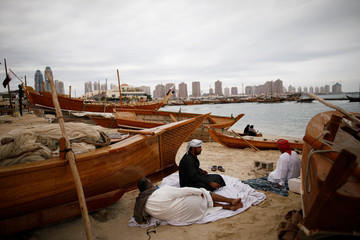 Muslim men rest between wooden boats on Katara beach in Doha
