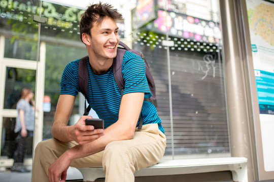 happy young man sitting at bus stop with cellphone in hand