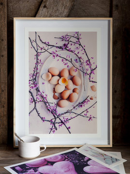Framed photo print of eggs and flowers with photo prints on table