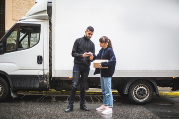 Young woman signing on smart phone while receiving package from mover